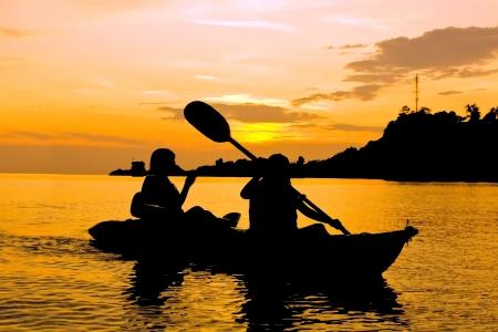 kayak: Silhouet van twee persoon kajakken in de zee bij zonsondergang in Koh Chang Thailand