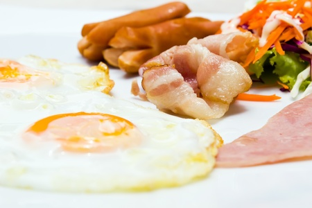 Breakfast eggs bacon and sausage with vegetable photo