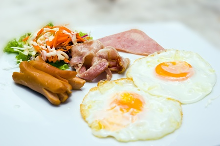 Breakfast food eggs bacon and sausage in plate