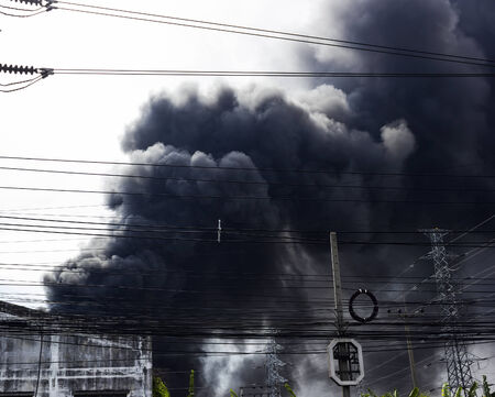 Black smoke from f ire burning in day time Stock Photo