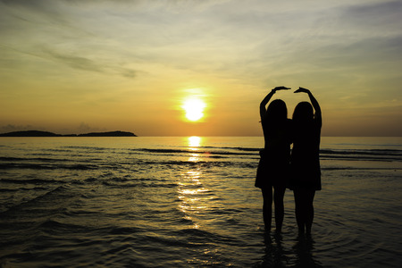 Relation of friend on the beach with sunrise