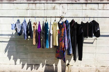 Clothes hang against wall to dry in suuny day Stockfoto