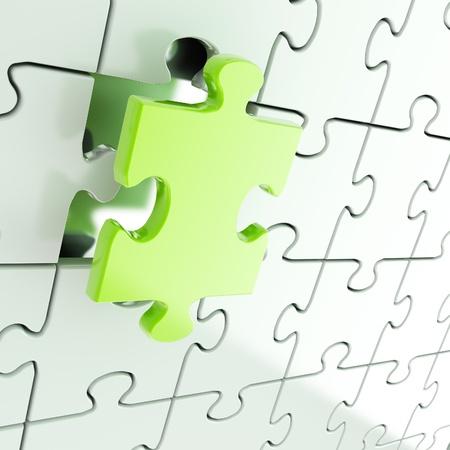 パズルのジグソー パズル 1 つが緑色の部分が目立つと光沢のある金属の背景 写真素材