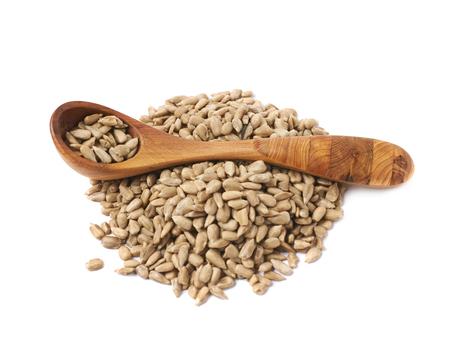 semilla: Pila de semillas de girasol con una cuchara de madera sobre ella, la composición aislada sobre el fondo blanco Foto de archivo