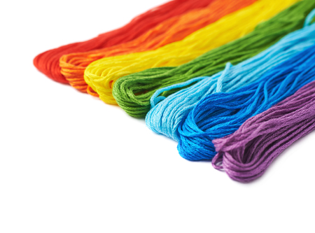 thread: Surface covered with multiple rainbow colored embroidery thread yarns isolated over the white as a copyspace background composition Stock Photo