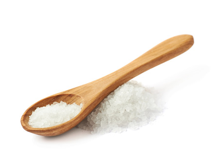 cuchara: cuchara de madera sobre la pila de sal de roca blanco, composición aislada sobre el fondo blanco
