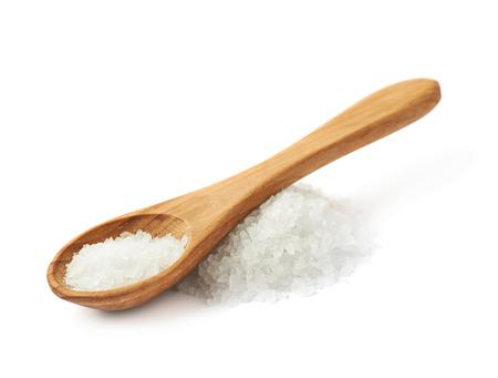 Houten lepel over de stapel van witte steen zout, samenstelling geïsoleerd over de witte achtergrond Stockfoto