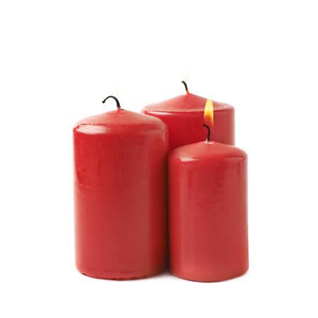 Drie brandende rode kaarsen, de samenstelling die over de witte achtergrond