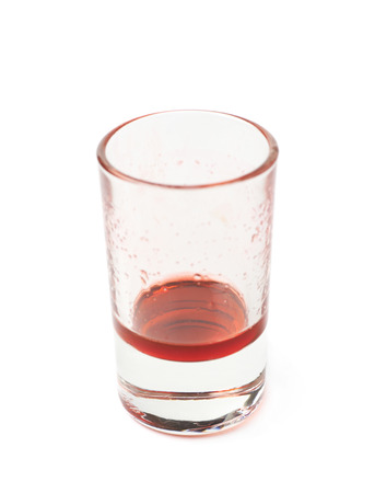 leftovers: Glass shot with grenadine red syrup leftovers isolated over the white background