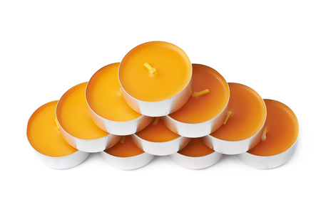 paraffin: Pyramid of tealight paraffin wax orange candles isolated over the white background