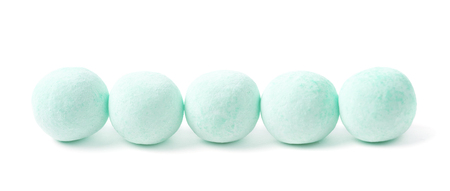 turqoise: Sugar coated glazed ball candies arranged in a line, composition isolated over the white background