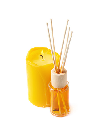 christmas perfume: Burning yellow wax candle and aroma sticks in a vial, composition isolated over the white background Stock Photo