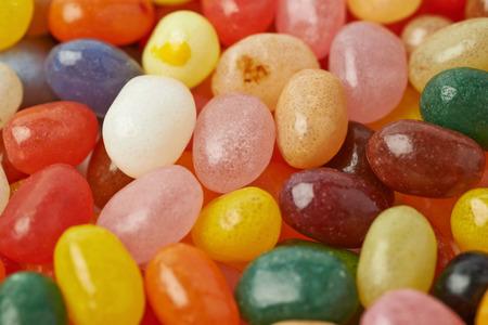 niños comiendo: Superficie cubierta con varios caramelos de colores haba de jalea como una composición telón de fondo