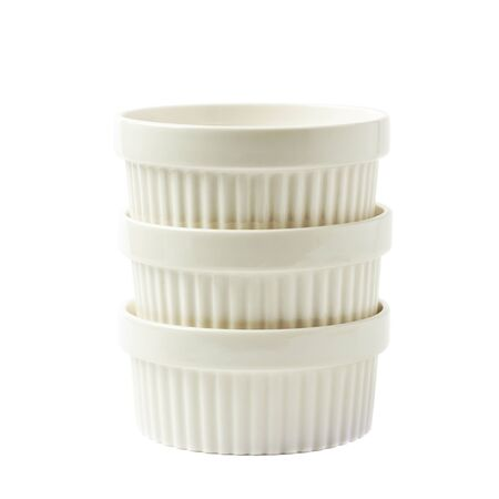 ramekin: Pile of multiple white porcelain souffle ramekin dishes isolated over the white background