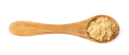 cuillère de mesure en bois pleine de poudre de cuisson au gingembre isolé sur fond blanc Banque d'images