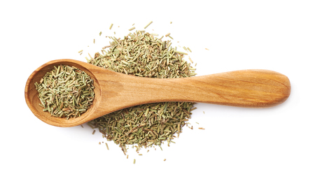 Pile of dried rosmarinus seasoning with a wooden spoon on top of it, compostion isolated over the white background Stock Photo