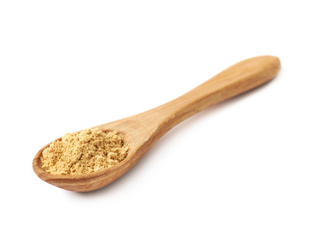 measuring spoon: Wooden measuring spoon full of ginger cooking powder isolated over the white background Stock Photo