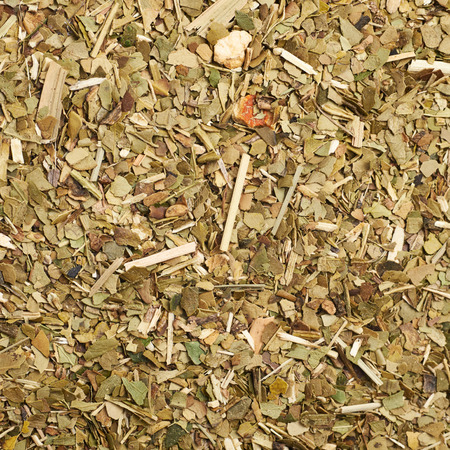 mate: Surface covered with dry mate tea leaves as a background texture composition