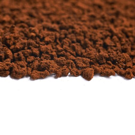caffiene: Surface coated with the instant coffee grains isolated over the white background as a copyspace backdrop composition Stock Photo