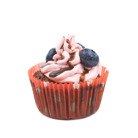 bilberries: Single chocolate muffin coated with the pink cream frosting and fresh bilberries, composition isolated over the white background