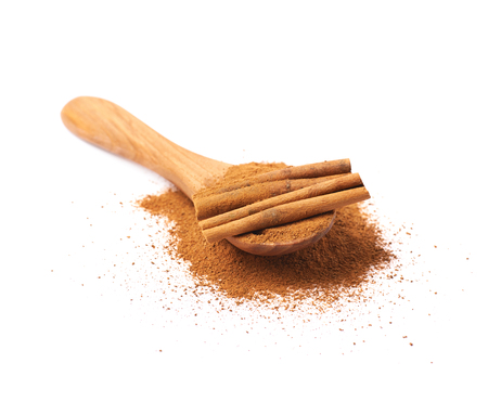 cinnamon bark: Pile of cinnamon powder with the wooden spoon and raw bark sticks on top of it, composition isolated over the white background