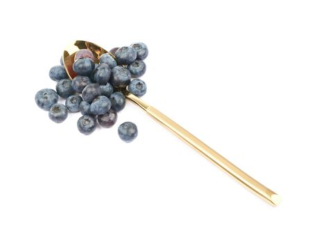 bilberries: Golden spoon full of bilberries isolated over the white background Stock Photo