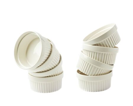 ramekin: Pile of multiple white porcelain souffle ramekin dishes isolated over the white background, set of two different foreshortenings
