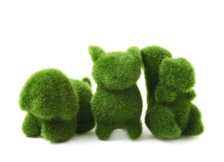 statuettes: Toy animal statuettes made of plastic green grass as an Easter decoration, composition isolated over the white background Stock Photo