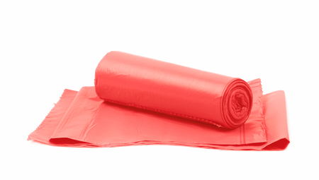 degradable: Red plastic polyethylene trash bag roll isolated over the white background
