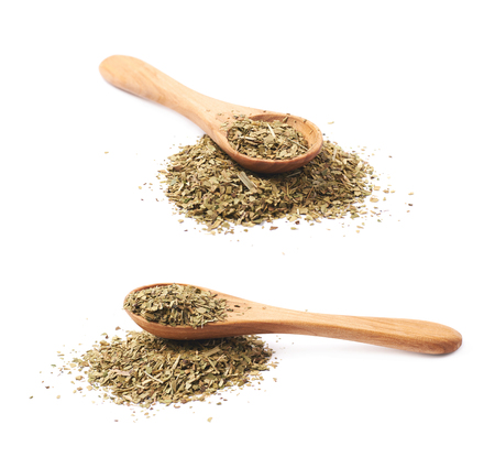 Pile of dry mate tea leaves with a wooden spoon over it, composition isolated over the white background, set of two different foreshortenings