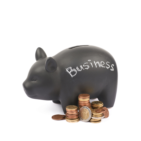 Word Business written with chalk on a black ceramic piggy bank coin container next to a pile of euro coins, composition isolated over the white background
