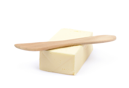 butterfat: Wooden knife over a briquette piece of a butter, composition isolated over the white background Stock Photo