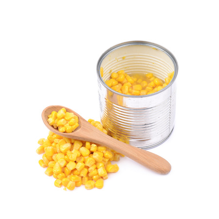 Tincan with a pile of canned corn and a wooden spoon next to it, composition isolated over the white background Stock Photo
