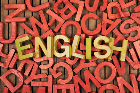 old english: Word English made of green wooden block letters over the pile of red ones