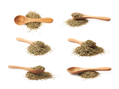 Pile of dry mate tea leaves with a wooden spoon over it, composition isolated over the white background, set of six different foreshortenings Stock Photo