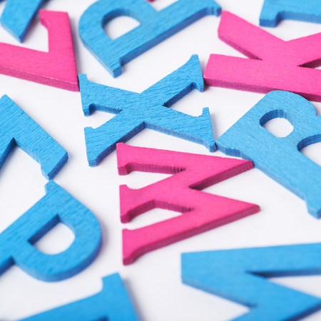 White surface covered with the multiple colorful blue and pink painted wooden letters as a backdrop composition Stock Photo