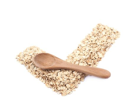 Yes tick shape made of oatmeal flakes with a wooden spoon over it, composition isolated over the white background