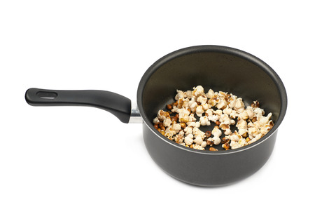 Black cooking pot filled with the burnt popcorn leftovers, composition isolated over the white background