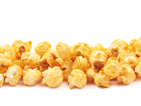 Line pile of the cheese flavoured orange popcorn flakes isolated over the white background, close-up crop composition