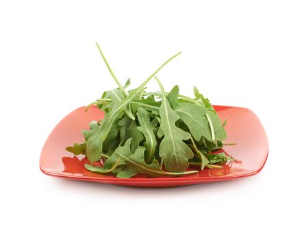 rukola: Red ceramic plate full of rocket salad leaves isolated over the white background