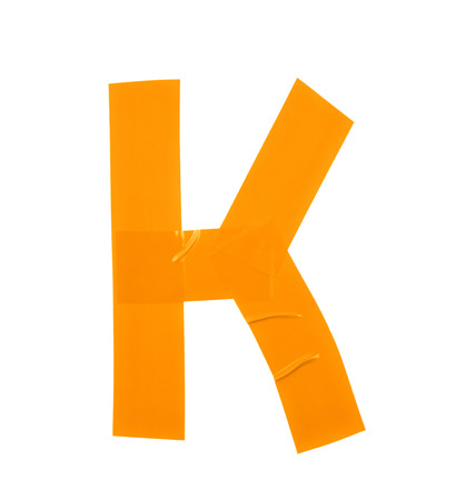 Letter K symbol made of insulating tape pieces, isolated over the white background Stock Photo