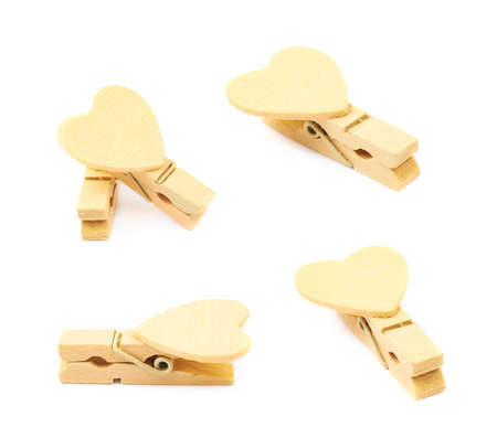Tiny heart shaped colored wooden peg pin isolated over the white background, set of four different foreshortenings