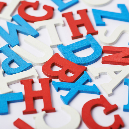 White surface covered with the multiple colorful red, blue, white painted wooden letters as a backdrop composition Stock Photo