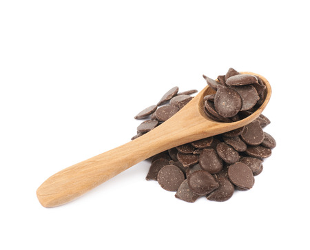 morsels: Pile of cooking chocolate teardrop shaped chips with a serving wooden spoon over it, composition isolated over the white background