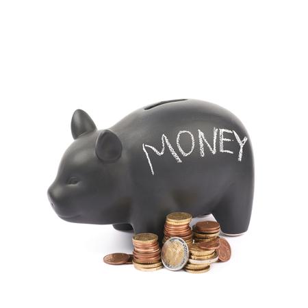 Słowo pieniądze pisać z kredą na czarnym ceramicznym prosiątko bank monety kontenerze obok stosu euro monety, skład odizolowywający nad białym tłem Zdjęcie Seryjne