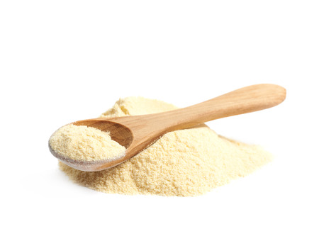 measuring spoon: Pile of corn flour with a wooden measuring spoon over it, composition isolated over the white background Stock Photo