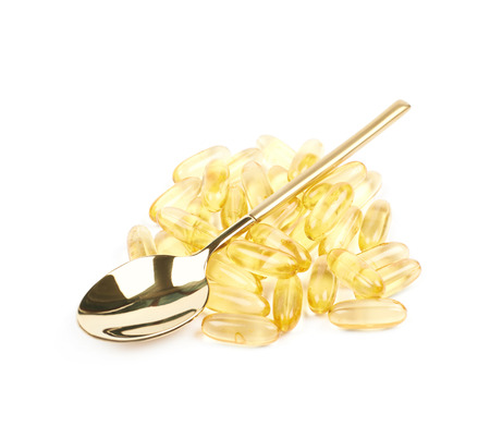 Pile of yellow softgel medical pills with a golden spoon over it, composition isolated over the white background