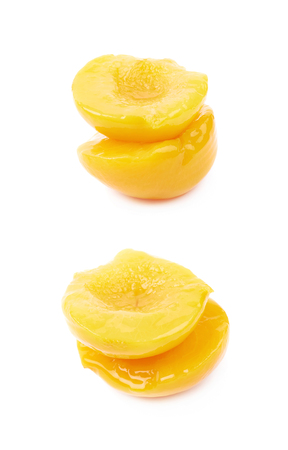compostion: Two canned peach fruits halves, compostion isolated over the white background, set of two different foreshortenings Stock Photo