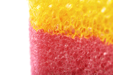 bath sponge: Red and yellow colored bath sponge isolated over the white background, close-up crop fragment as a copyspace backdrop composition Stock Photo