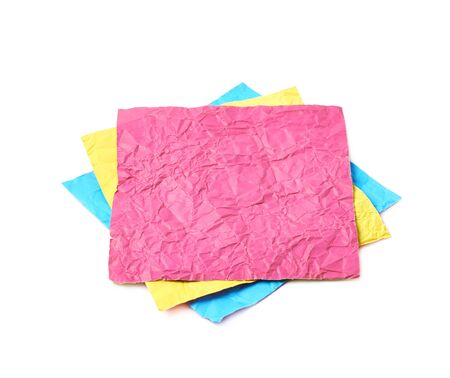 Three crumpled origami square paper sheets, cmyk colored, composition isolated over the white background
